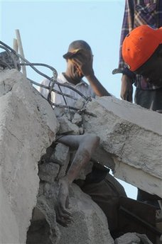 A man gestures behind a person trapped in the rubble of a collapsed building in Port-au-Prince